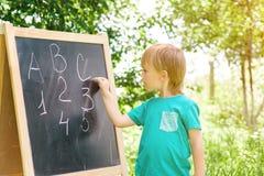 Nette Schreibensbuchstaben und -zahlen des kleinen Jungen an der Tafel im Garten Stockfotos