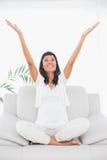 Nette schwarze behaarte Frau in der weißen Kleidung, die ihre Arme anhebt Stockfotografie
