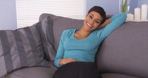 Nette schwarze Frau, die auf dem Couchlächeln stillsteht Stockbilder