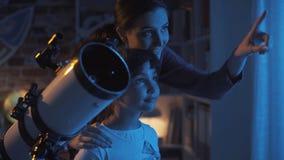 Nette Schwestern, welche die Sterne mit einem Teleskop aufpassen stockfotografie