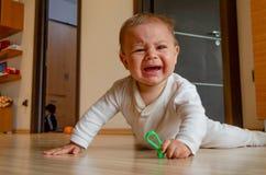 Nette sechs Monate alte Baby, die Bauchzeit auf dem Boden haben und f?r Aufmerksamkeit schreien lizenzfreies stockbild