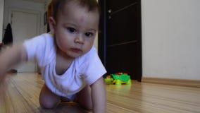 Nette sieben Monate alte Baby, die das Kriechen, Transportwagen heraus lernen, schossen stock video footage