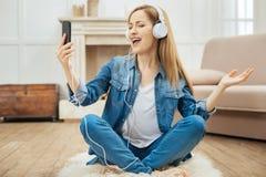 Nette singende Frau beim Hören Musik Stockbild