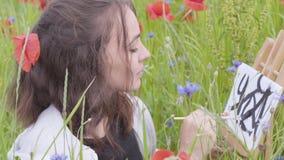 Nette smilling Mädchenmalerei mit schwarzen Farben auf dem Mohnblumenfeld Junges Künstlerinfreien Verbindung mit Natur stock video footage