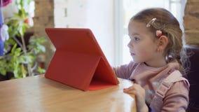 Nette Spielspiele des kleinen Mädchens auf der digitalen Tablette stock video footage