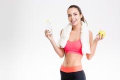 Nette Sportlerin, die eine Flasche des Wassers und des Apfels hält Lizenzfreie Stockfotografie