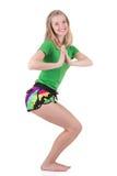 Nette sportliche blonde Frau, die in der Sportkleidung hockt mit dem verdrehten Torso mit den Händen vor Kasten trägt Lizenzfreie Stockfotografie