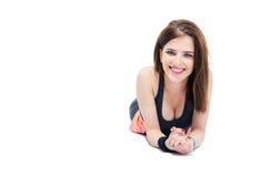 Nette sportliche junge Frau, die auf dem Boden liegt stockfotos