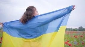 Nette Stellung des jungen Mädchens des Porträts auf einem Mohnblumengebiet umfasst mit Flagge von Ukraine Verbindung mit Natur, P stock footage