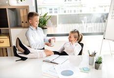 Nette stilvolle intelligente Kinder arbeiten im Büro Stockfoto