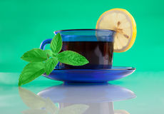 Nette Tasse Tee und Minze auf grünem Hintergrund Stockbild