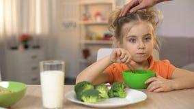 Nette Tochter, die Frühstückskost aus Getreide mit Milch, Mutter streicht Mädchenkopf isst stock video footage