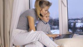 Nette Tochter mit ihrer Mutter, die Computer verwendet stock video footage