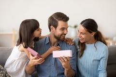 Nette Tochter und Frau, die glückliches Vateröffnungsgeschenk beglückwünscht stockbilder