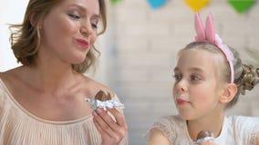 Nette Tochter und Mutter, welche die Schokoladeneier zusammen genießen Zeitvertreib, Familie isst stock footage