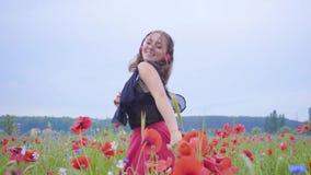 Nette tragende Kopfhörer der jungen Frau, die Musik hören und auf einem Mohnblumengebiet glücklich lächelt tanzen Verbindung mit stock footage