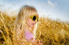 Nette tragende Sonnenbrille des kleinen Mädchens, an einem warmen Tag Stockfoto