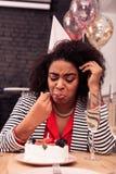 Nette traurige Frau, die ihren Geburtstagskuchen versucht lizenzfreie stockbilder