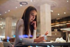 Nette und recht junge Frau auf Smartphone im Café stockfotografie
