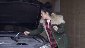 Nette ungeschickte Frau versucht, Automotor mit Schlüssel zu reparieren stock video footage