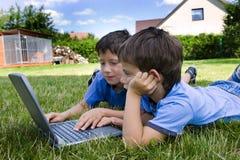 Nette Untersuchung des Jungen zwei über Computer lizenzfreies stockfoto