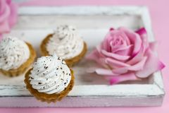 nette Vanillekleine kuchen auf hölzernem Behälter der Weinlese mit rosafarbenen Blumen Stockfotografie