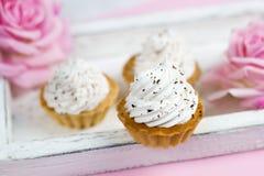 nette Vanillekleine kuchen auf hölzernem Behälter der Weinlese mit rosafarbenen Blumen Lizenzfreie Stockfotografie