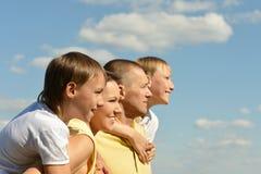 Nette vierköpfige Familie auf Himmel stockbilder