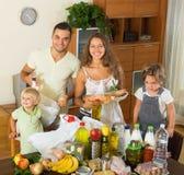 Nette vierköpfige Familie mit Taschen des Lebensmittels Stockfoto