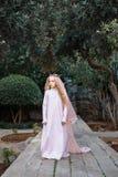 Nette weiße Zauberin der Märchen in einem magischen Wald geht entlang den Weg in einem Kleid und in einer Krone mit einem Schleie lizenzfreie stockfotos
