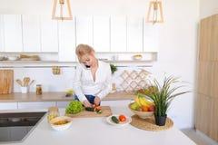Nette weibliche Hausfrau plaudert auf zellulärem und Lächeln, bereitet Salz vor Stockbilder