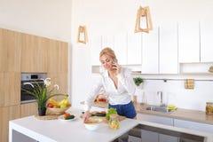 Nette weibliche Hausfrau plaudert auf zellulärem und Lächeln, bereitet Salz vor Lizenzfreie Stockbilder
