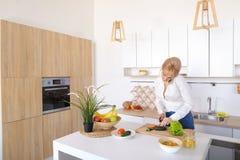 Nette weibliche Hausfrau plaudert auf zellulärem und Lächeln, bereitet Salz vor Stockfoto