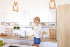 Nette weibliche Hausfrau plaudert auf zellulärem und Lächeln, bereitet Salz vor Lizenzfreies Stockfoto