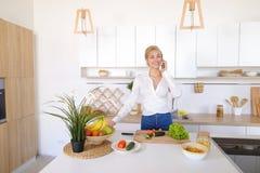 Nette weibliche Hausfrau plaudert auf zellulärem und Lächeln, bereitet Salz vor Lizenzfreie Stockfotografie