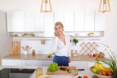 Nette weibliche Hausfrau plaudert auf zellulärem und Lächeln, bereitet Salz vor Stockfotos