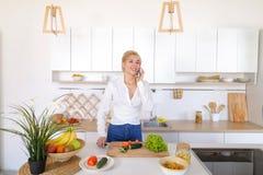 Nette weibliche Hausfrau plaudert auf zellulärem und Lächeln, bereitet Salz vor Lizenzfreie Stockfotos