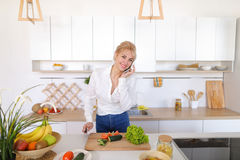 Nette weibliche Hausfrau plaudert auf zellulärem und Lächeln, bereitet Salz vor Stockfotografie