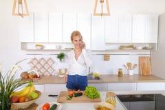Nette weibliche Hausfrau plaudert auf zellulärem und Lächeln, bereitet Salz vor Lizenzfreies Stockbild