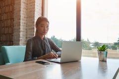 Nette weibliche schauende Kamera während der Arbeit über Laptop-Computer Stockbild
