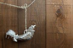 Nette Weihnachtsvogeldekoration, die an einem hölzernen Hintergrund hängt Lizenzfreie Stockfotos