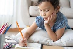 Nette zeichnende Hausarbeit des kleinen Mädchens und Schreiben mit Stift auf Papier in ihr Haus lizenzfreies stockbild