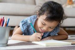 Nette zeichnende Hausarbeit des kleinen Mädchens und Schreiben mit Stift auf Papier in ihr Haus lizenzfreies stockfoto