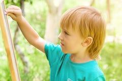 Nette Zeichnung des kleinen Jungen auf Tafel mit der Kreide, im Freien am sonnigen Tag des Sommers Stockbild