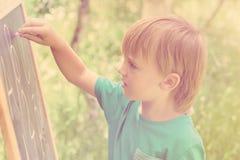 Nette Zeichnung des kleinen Jungen auf Tafel mit der Kreide, im Freien am sonnigen Tag des Sommers getont Stockfotografie