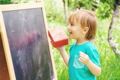 Nette Zeichnung des kleinen Jungen auf Tafel mit der Kreide, im Freien am sonnigen Tag des Sommers Zurück zu Schule-Konzept Stockbild