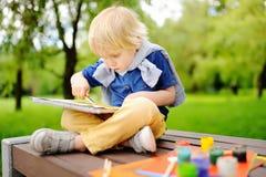 Nette Zeichnung des kleinen Jungen mit bunten Farben im Sommerpark Lizenzfreie Stockfotos