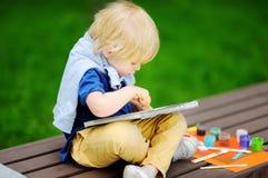 Nette Zeichnung des kleinen Jungen mit bunten Farben im Sommerpark Lizenzfreies Stockfoto
