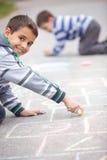 Nette Zeichnung des kleinen Jungen mit Kreide draußen Stockfotografie