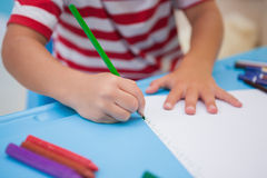 Nette Zeichnung des kleinen Jungen am Schreibtisch Stockbilder